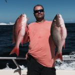 man holding two fish on charter
